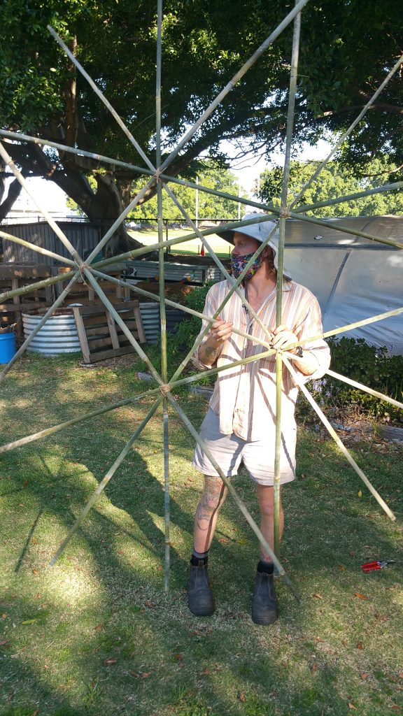 Man holding star shaped woven bamboo.